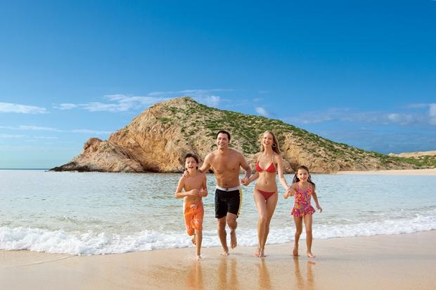 A family runs on the beach at Los Cabos, Baja California