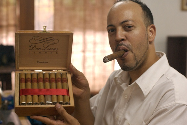 A man with a cigar showing off a cigar box at the Don Lucas Cigar Shop in Punta Cana