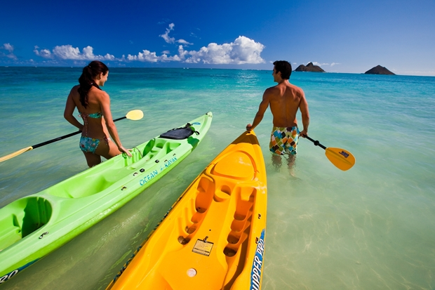 A couple gets ready to set out on kayas in Oahu