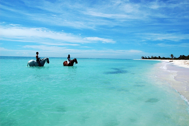 A couple horseback riding in the middle of the Caribbean Sea off the coast of the Riviera Maya