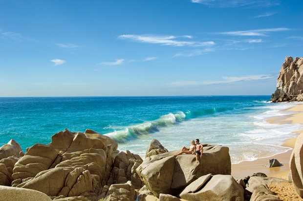 Here a couple relaxes on the rocks at Lover's Beach in Los Cabos