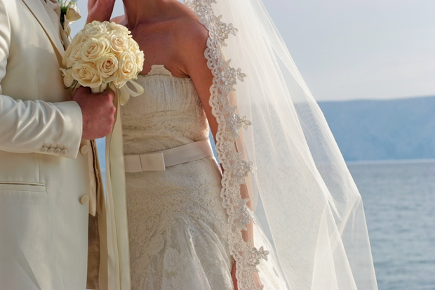A bride and groom taking their vows at a beach wedding