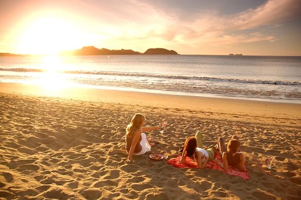Three women at a beach in Guanacaste, Costa Rica, enjoying a beautiful sunset