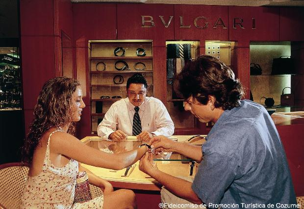 A man helps a woman try on a watch at a BVLGARI store on Cozumel Island, Mexico