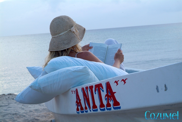 A woman sits in a small boat called Anita while she comfortably reads a book at the beach on Cozumel Island, Mexico