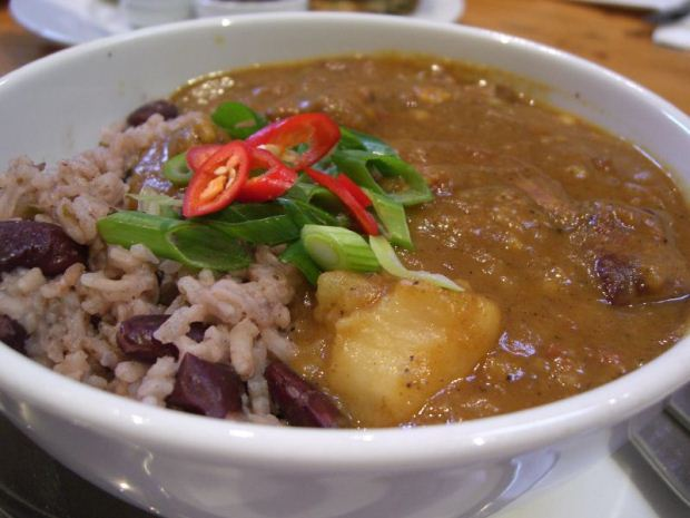 A plate of Jamaican curried goat serve with rice and beans in coconut milk
