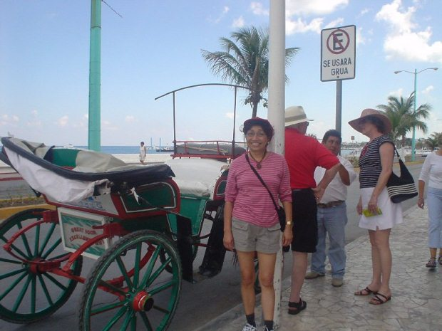 A family standing before a horse-drawn carriage on Cozumel island in Mexico.