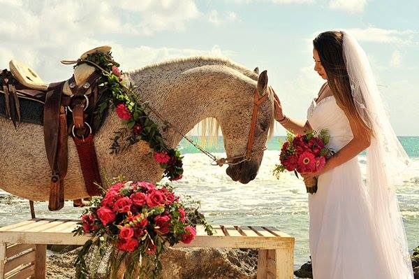 A bride carressing a horse at the beach in the Riviera Maya, Mexico