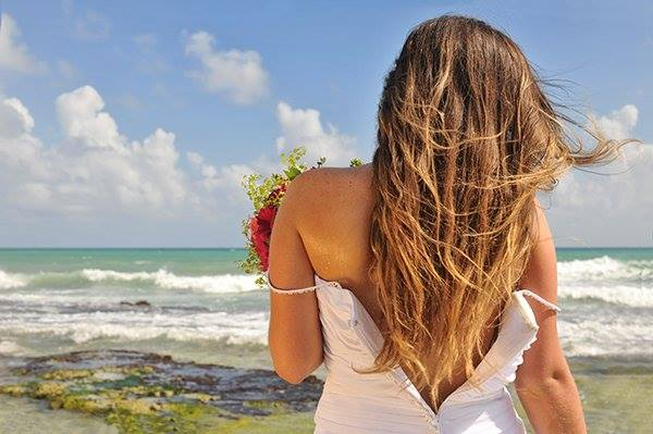 A bride holding a flower arrangement as she looks out to the Caribbean Sea in Mexico's Riviera Maya