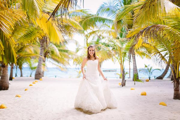 A bridal model walking down the white sand aisle in front of the Caribbean Sea at Mexico's Riviera Maya