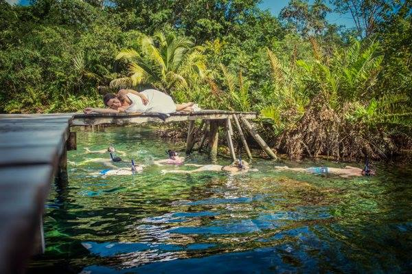 A bride rests upon a pier of a cenote as snorkelers swim by in the Riviera Maya, Mexico