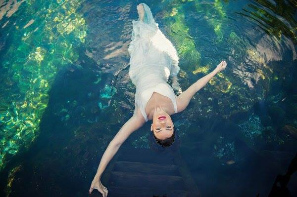 A bridal model holds on to a ladder as she looks up into the camera at a cenote in Mexico's Riviera Maya