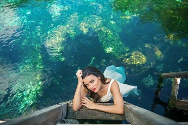 A newlywed bride looking up at the camera from within the cool waters of a Maya cenote in the Mexican Caribbean
