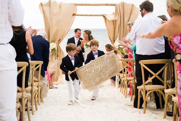 """two children walk down the white sand aisle holding a sign that says """"Happily Ever After"""" at a destination wedding on the beach in the Riviera Maya"""
