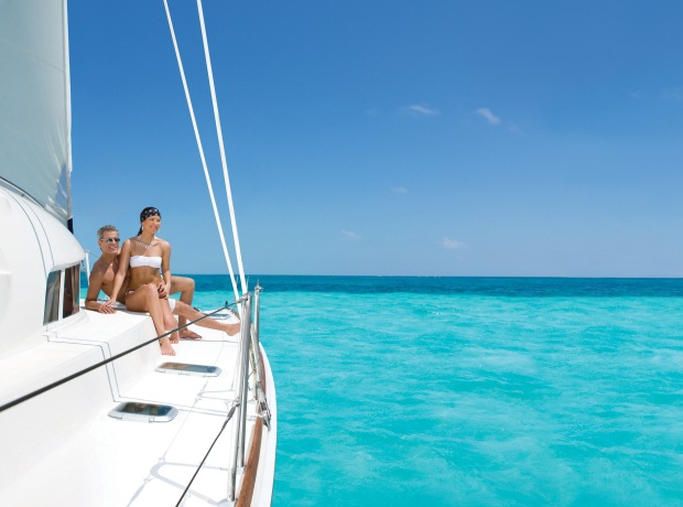 A couple relaxes on a luxury catamaran in the Caribbean Sea during their honeymoon in the Riviera Maya, Mexico