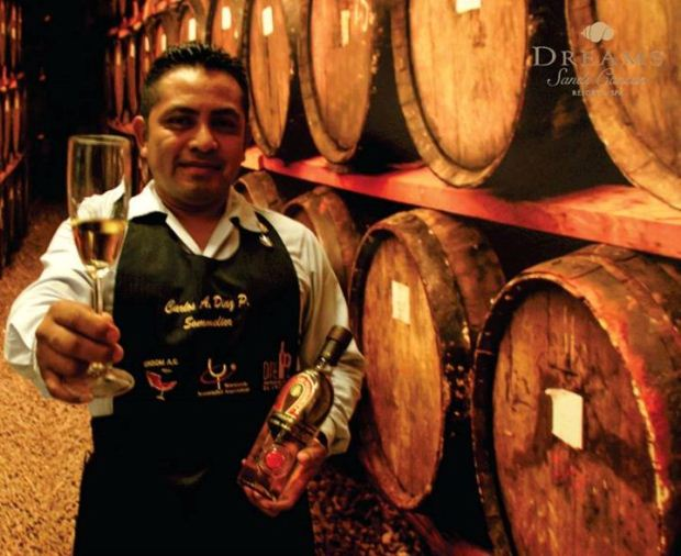 Tequila expert at Dreams Sands holding out a shot of tequila to guests while standing in front of several wooden barrels filled with aged tequila