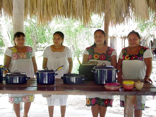 A group of Maya women stand in front of the food they prepared for the guests of the Ek Balam tour