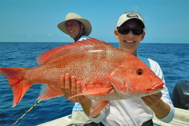 A woman holds up her catch of the day from a fishing trip off the coast of Cancun, Mexico