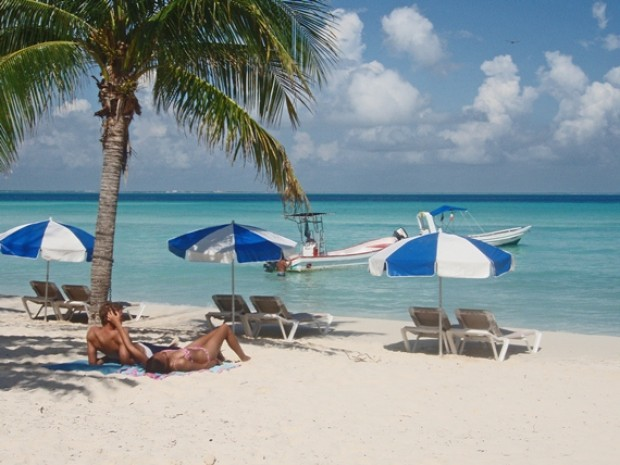 Tourists relax under a palm tree on Isla Mujeres island as part of the numerous Cancun family activities available at this international tourist hub