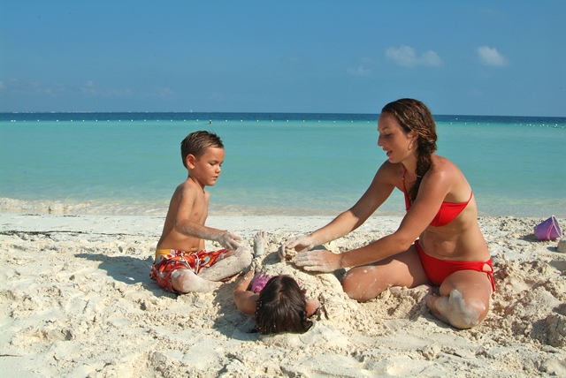 A family playing in the sand on the beach in Cancun during their Mexico Family Vacations