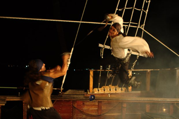 A pirate makes an aerial assault on another pirate on an Amstar dmc pirate tour aboard the Jolly Rogers boat