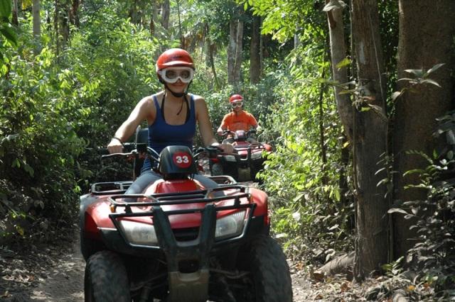 Tourists race through the jungle on the ATV tour on Cozumel Island, Mexico