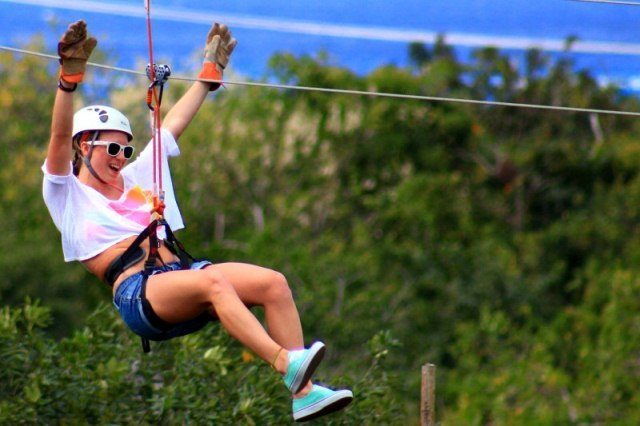 A girl zips high over the jungle canopy overlooking the Caribbean Sea on Mexico's Cozumel Island