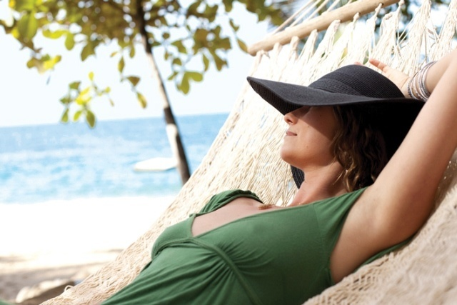 A woman relaxes in a hammock over looking the Pacific Ocean on an Amstar tour of Las Caletas in Puerto Vallarta