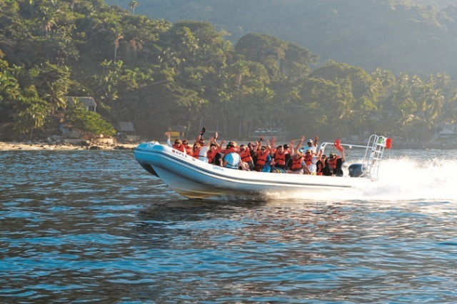 A group of tourists travel in a speedboat organized by Amstar dmc for the Outdoor Adventure tour in Puerto Vallarta.