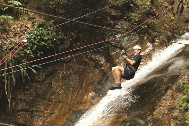 A man zip lines over a waterfall in the Sierra Madre Mountains just outside of Puerto Vallarta on the Outdoor Adventure tour organized by Amstar dmc.