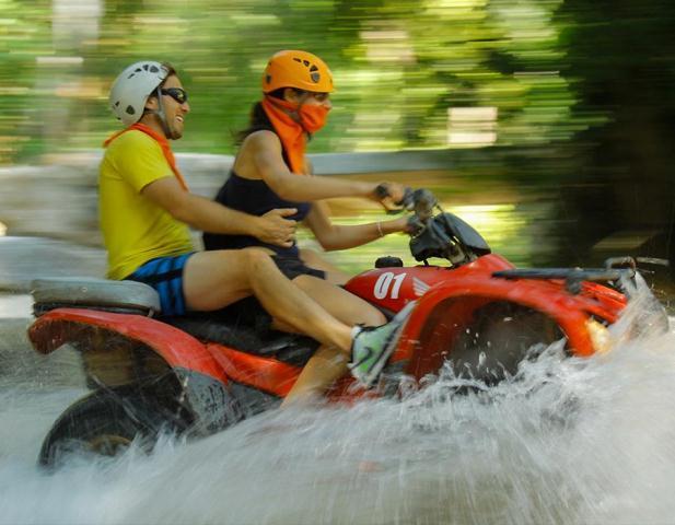 A couple races through the Sierra Madre Mountains aboard an ATV on the Amstar dmc ATV tour.