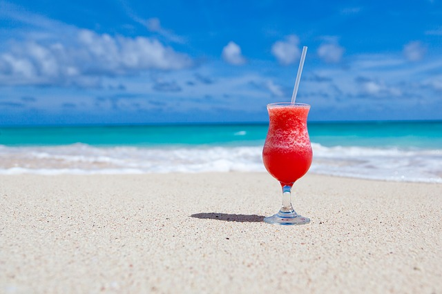 A frozen daquiri is placed on the sand in front of the Caribbean Sea at Bayahibe Beach in La Romana, Dominican Republic
