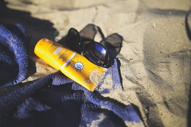 A bottle of sunscreen, sunglasses and a towel lying on a beach
